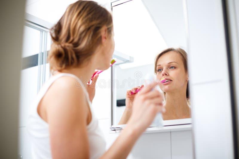 相当女性刷她的在镜子前面的牙 库存照片