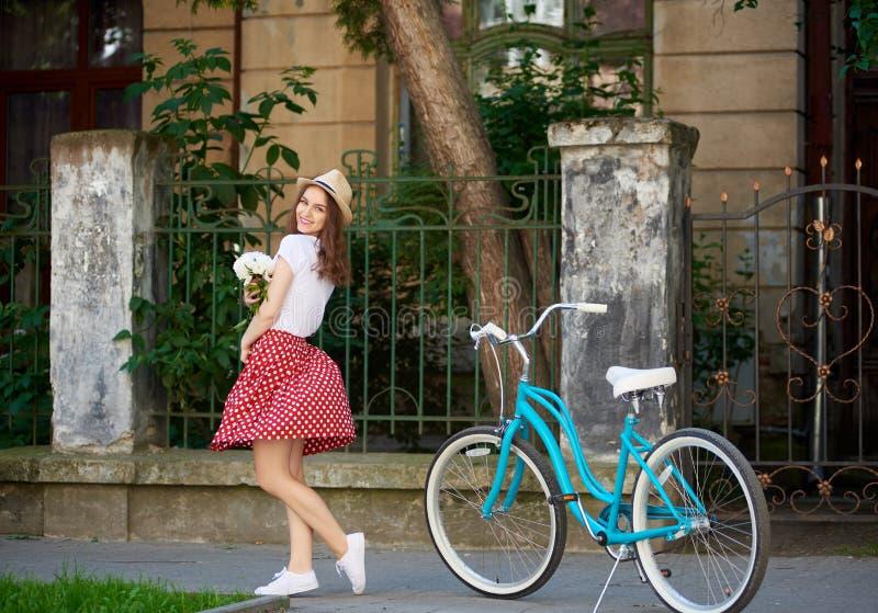 相当女性在红色礼服在她的在美丽的老房子前面的身分附近拿着与蓝色葡萄酒自行车的花 免版税库存图片