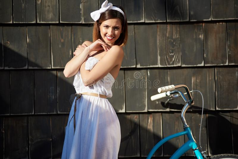 相当女性摆在与在黑暗的木墙壁附近的蓝色自行车 库存图片