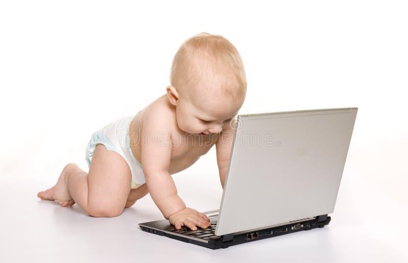 相当婴孩接近的膝上型计算机工作 免版税库存图片