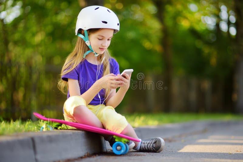 相当学会的小女孩踩滑板在美好的夏日在公园 享受踩滑板的乘驾的孩子户外 免版税库存图片