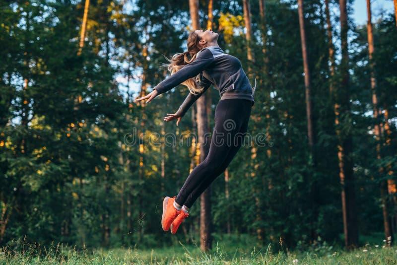 相当实践女性的体操运动员户外做弯跃迁 库存图片