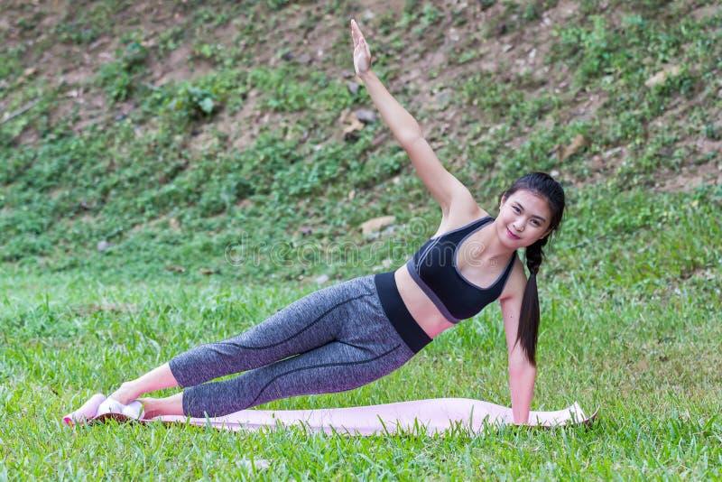 相当实践旁边板条瑜伽姿势的亚裔女孩 库存照片