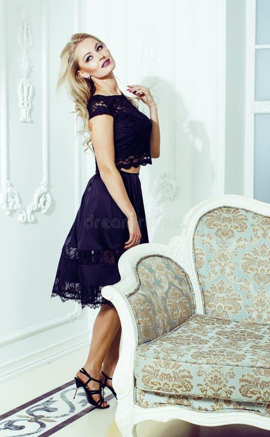 相当富有的豪华房子内部的白肤金发的妇女,时尚人 免版税库存照片