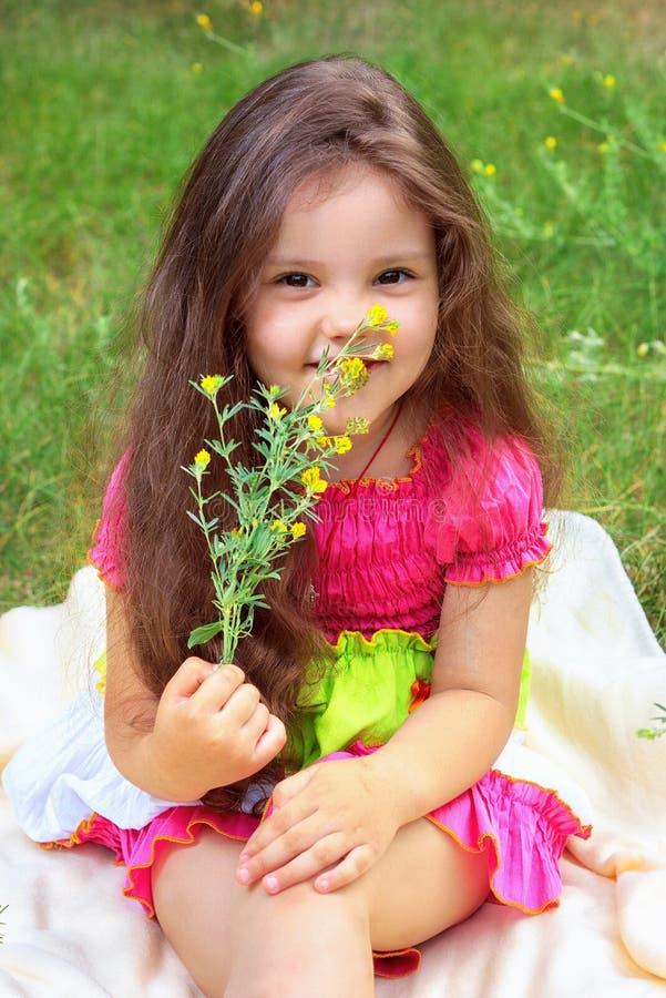 相当小女孩嗅到的花 免版税库存图片