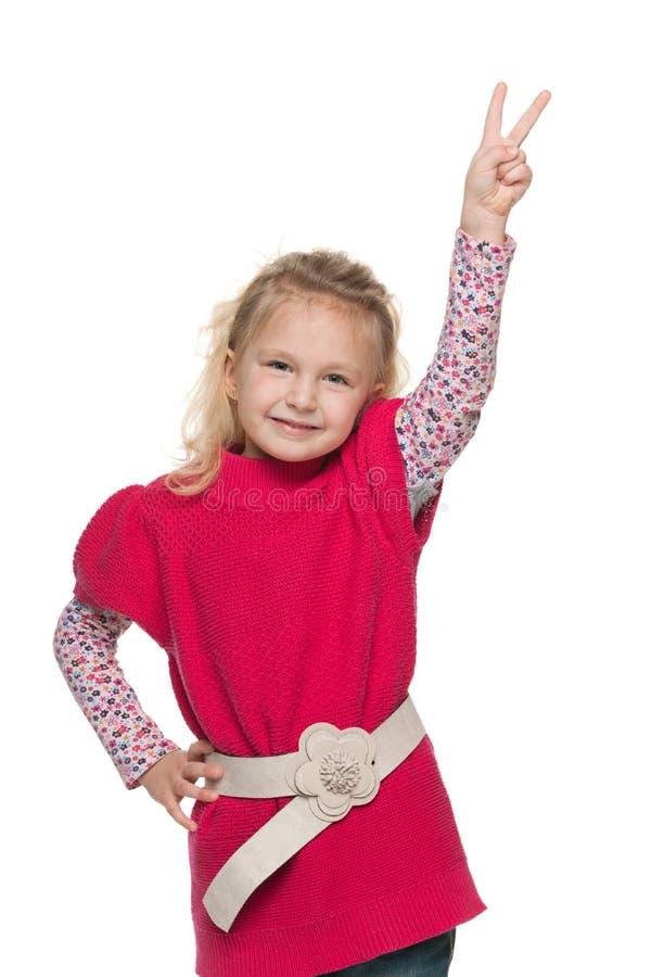 相当小女孩显示胜利标志 免版税库存照片