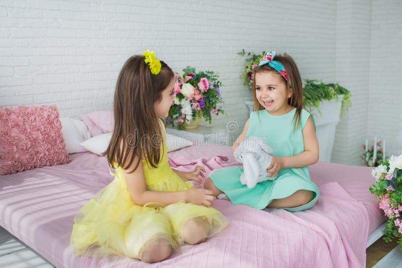 相当小女孩以黄色和绿松石礼服在一张床上使用在演播室 免版税库存图片