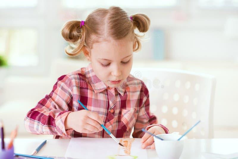 相当小孩与五颜六色的油漆的女孩绘画在家 免版税库存图片