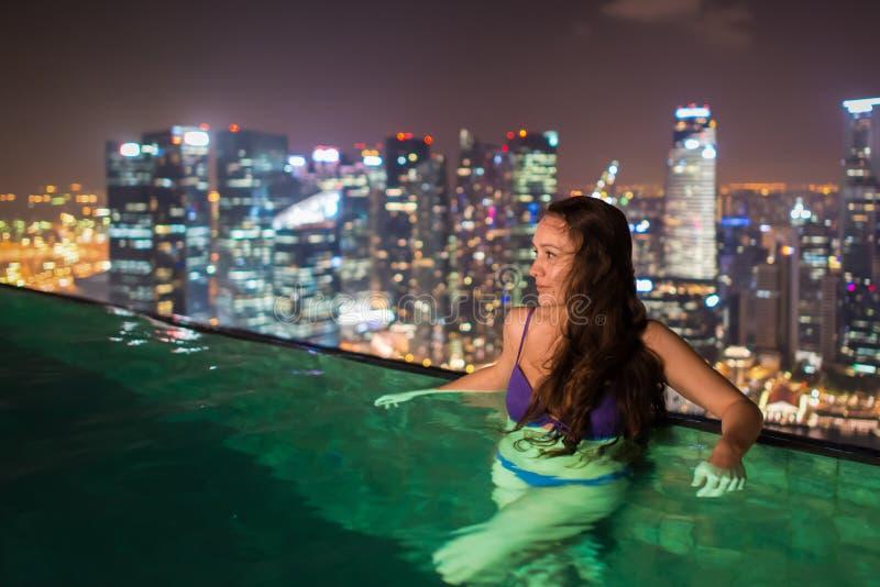 相当少妇游泳在屋顶的无限水池 库存照片