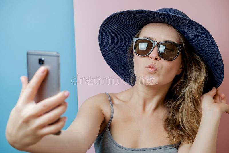 相当帽子和太阳镜的少妇有电话的 浓缩的夏天 免版税库存照片