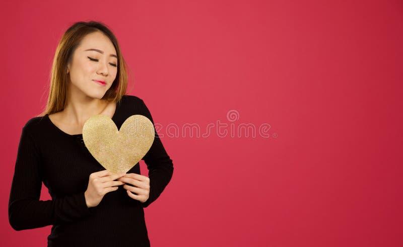 相当年轻亚裔妇女在拿着金心脏的演播室对她 库存图片