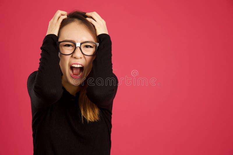 相当年轻亚裔妇女在演播室尖叫对照相机 库存照片