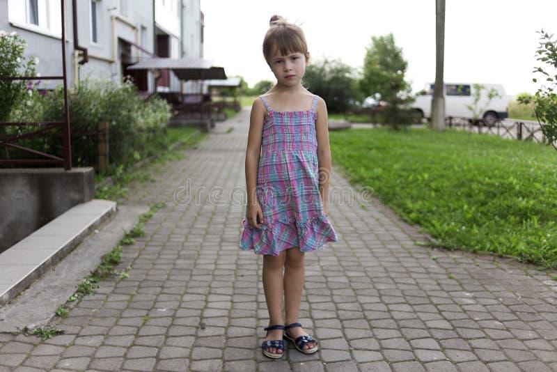 相当年轻以前单独站立在晴朗的路面的偶然夏天礼服的矮小个白肤金发的不快乐的喜怒无常的没有朋友的儿童女孩 免版税库存照片