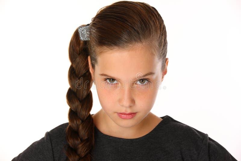 相当年轻女小学生特写镜头画象  她是严肃和过分要求的 图库摄影
