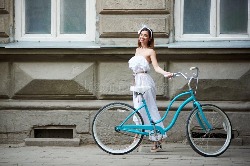 相当年轻女性摆在与在老历史大厦前面的蓝色自行车 库存照片