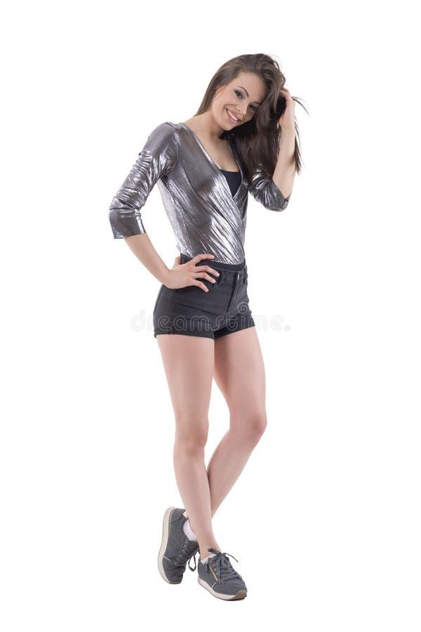 相当年轻深色的妇女在时髦的夏天给摆在和微笑穿衣 图库摄影