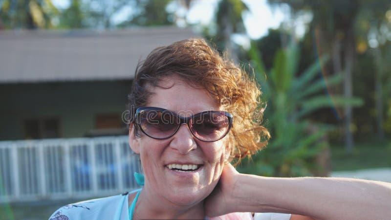 相当年迈的佩带的太阳镜的成熟妇女享用夏天太阳的 获得愉快的微笑的妇女在旅行的风的乐趣  免版税库存图片