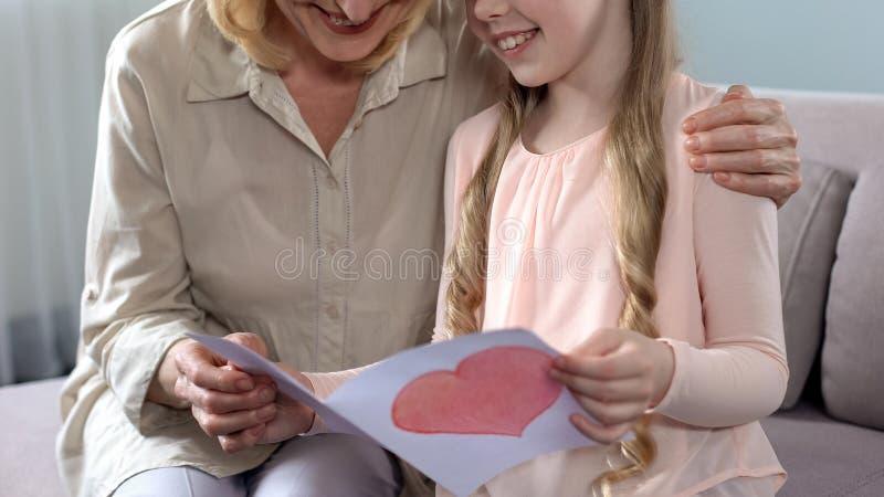 相当当前手工制造贺卡的一点女性孩子对祖母,生日 免版税图库摄影