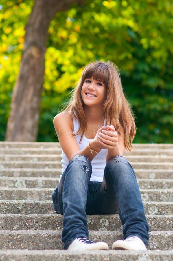 相当微笑的十几岁的女孩坐台阶 免版税库存图片