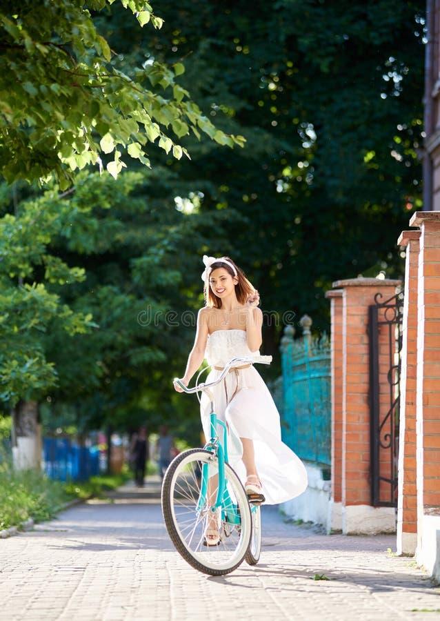 相当微笑的女性骑马蓝色自行车下来绿化公园胡同 免版税库存图片