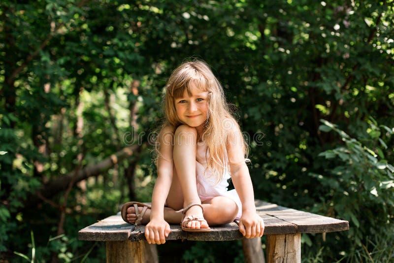 相当微笑的沉思女孩坐老桥梁 免版税库存图片