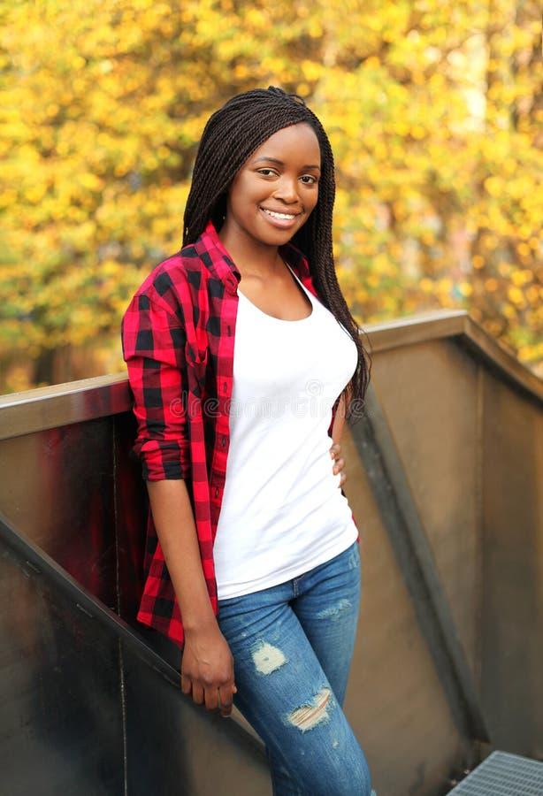 相当微笑的非洲妇女在晴朗的秋天的穿红色方格的衬衣 免版税图库摄影