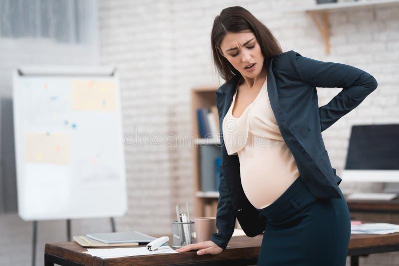 相当怀孕的女孩在办公室体验劳方 怀孕在办公室 库存图片