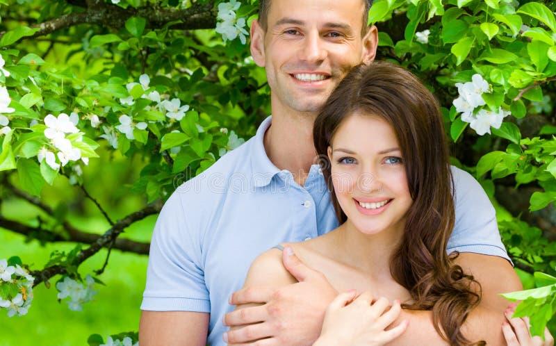 相当拥抱在开花的树附近的年轻夫妇 免版税库存图片