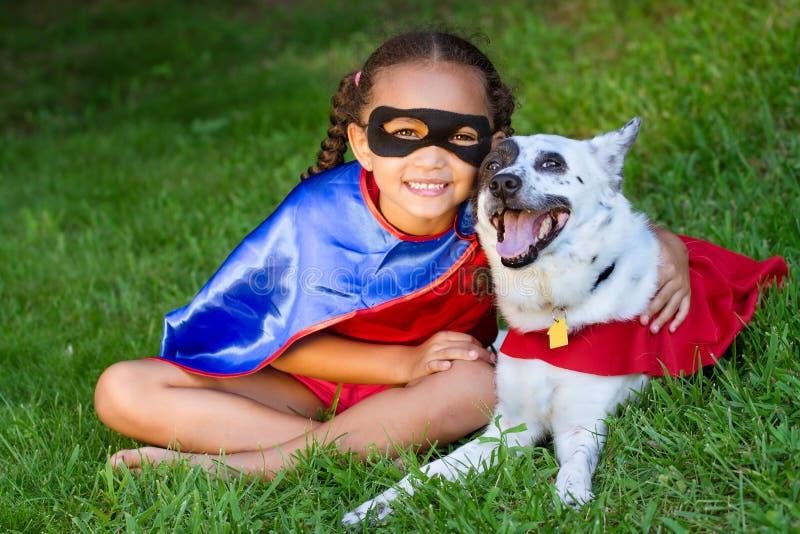相当拥抱她的宠物的混合的族种女孩 库存照片