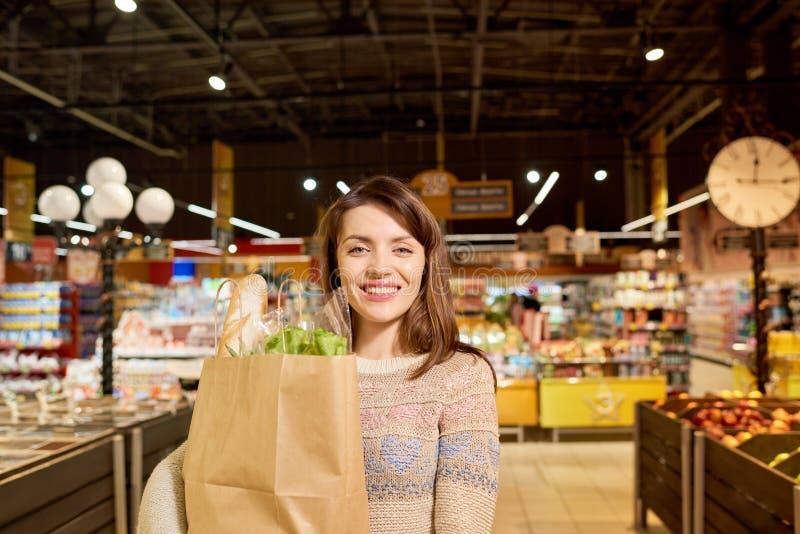 相当拿着食品杂货袋的少妇 免版税库存照片
