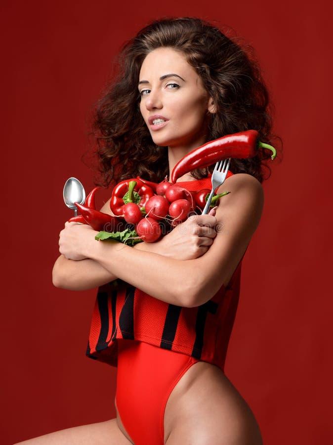 相当摆在与新鲜的红色菜萝卜辣椒绿色散叶莴苣荷兰芹叉子和匙子的少妇 免版税库存照片