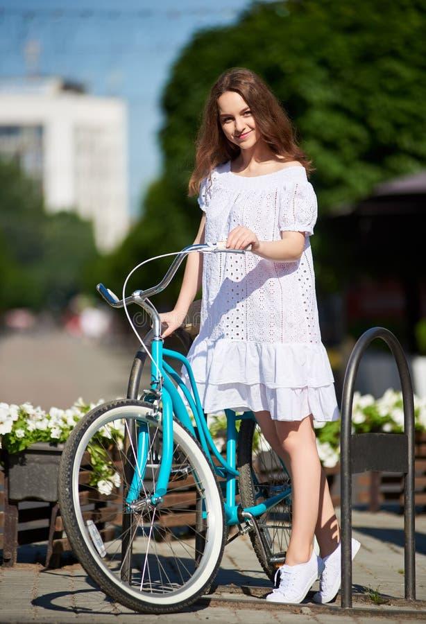 相当摆在她的在城市街道上的葡萄酒蓝色自行车旁边的白色礼服的女孩在晴朗的夏日期间 图库摄影