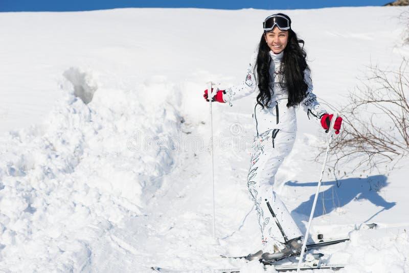 相当摆在她的滑雪齿轮的少妇 库存照片