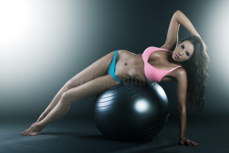相当放置在适应球的少妇,执行锻炼 免版税库存照片