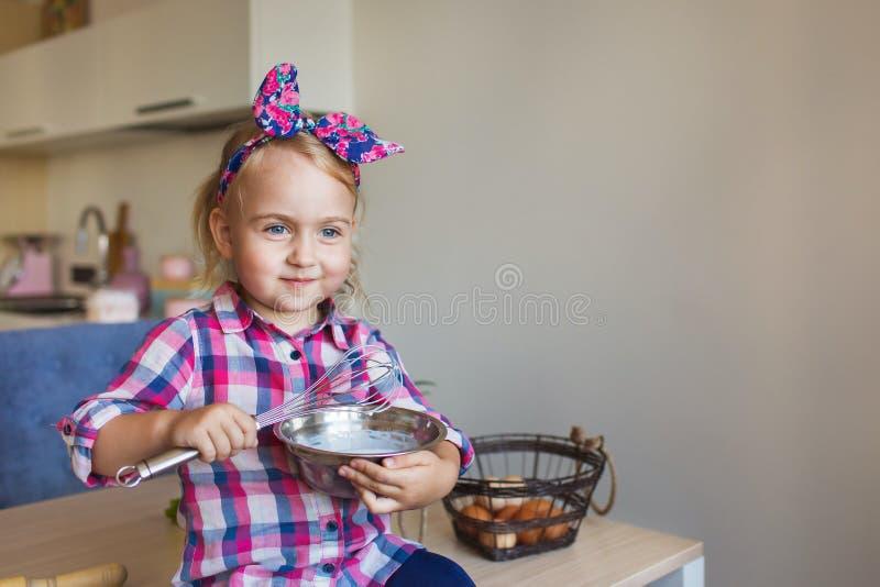 相当方格的衬衣的小女孩画象激起在厨房的奶油 免版税库存照片