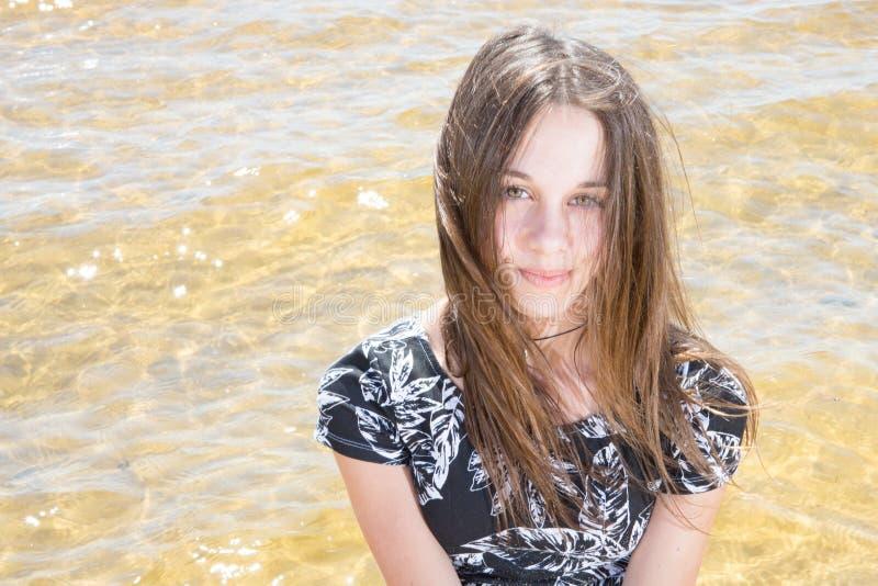 相当时兴的十几岁的女孩佩带的礼服在海边穿衣 免版税图库摄影