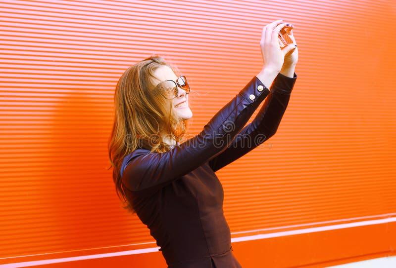 相当时髦的妇女在智能手机做自画象 库存图片