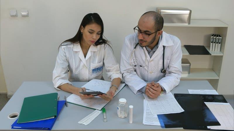 相当显示某事在数字式片剂的年轻护士对她的男性同事 库存照片