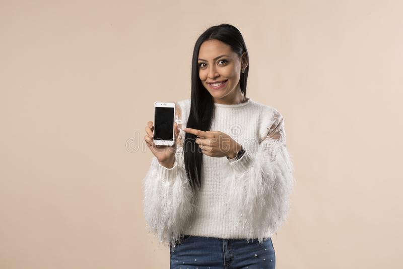 相当显示电话屏幕的年轻拉提纳妇女 免版税库存照片