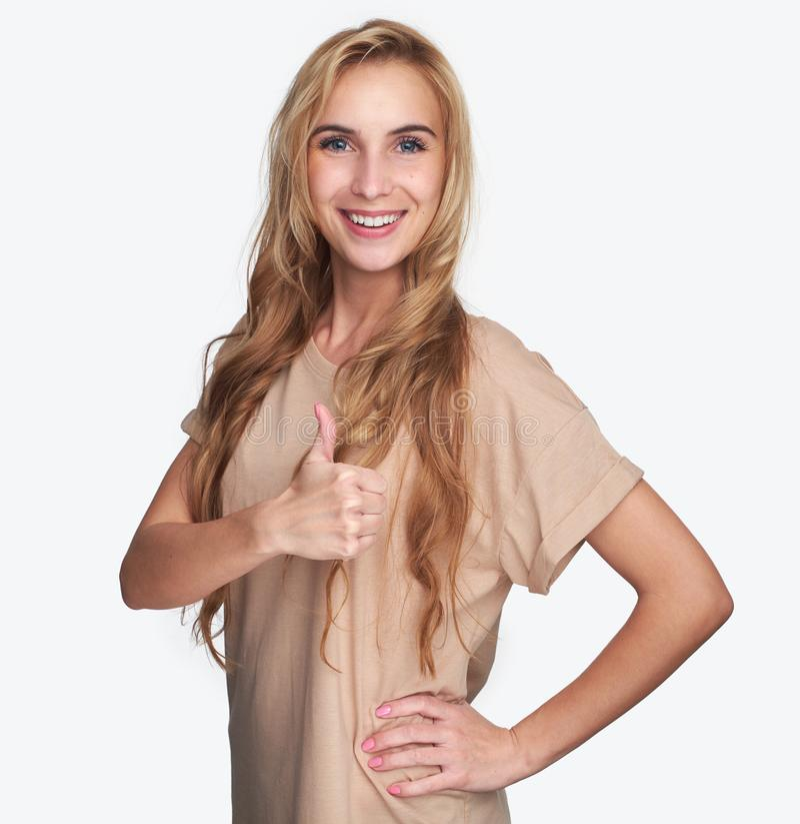 相当显示赞许标志的白肤金发的女孩 免版税库存照片