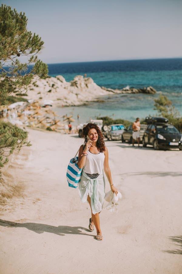 相当有一个袋子的少妇使用在海滩的手机 库存图片