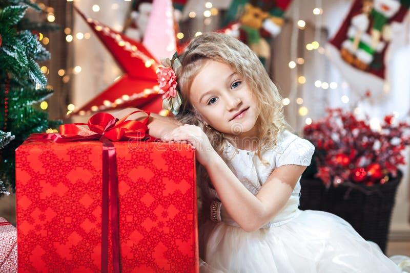 相当有一花发夹和米黄礼服坐的倾斜的小白肤金发的女孩在圣诞树附近的一件大红色礼物 图库摄影