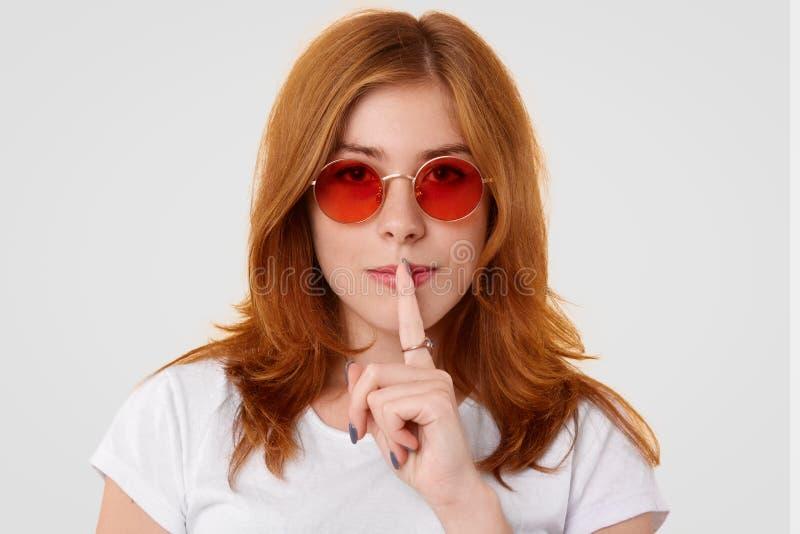 相当有严肃的表示的年轻女性特写做沈默标志,秘密地看照相机,告诉私有信息或 图库摄影