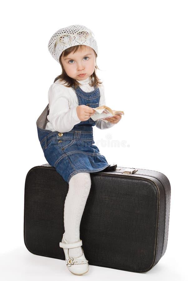 相当有书的小女孩坐手提箱和噘嘴 免版税库存图片