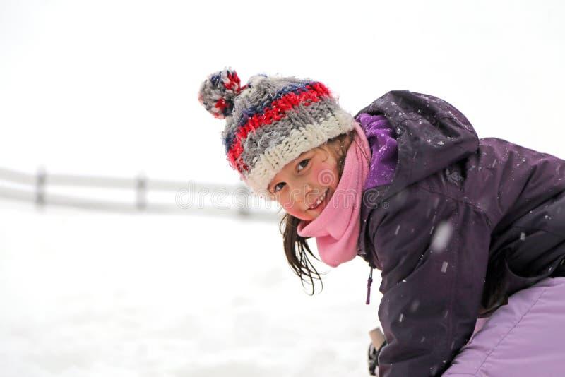 相当有使用在雪的羊毛贝雷帽的小女孩在冬天 免版税库存照片