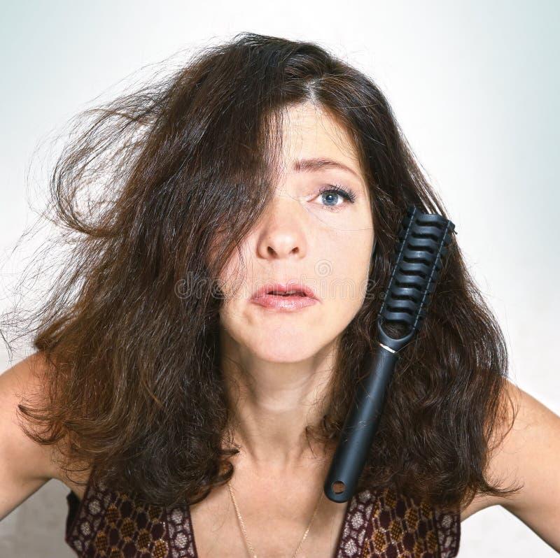 相当有刷子梳子的少妇在头发黏附了 免版税库存图片