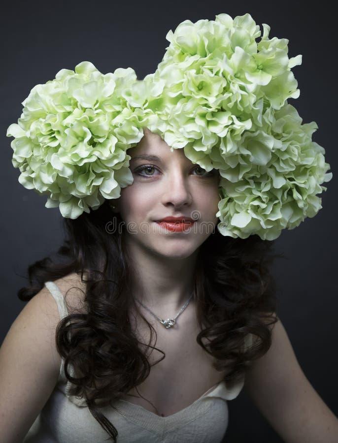 相当有大花的十几岁的女孩在她的头发 免版税库存照片