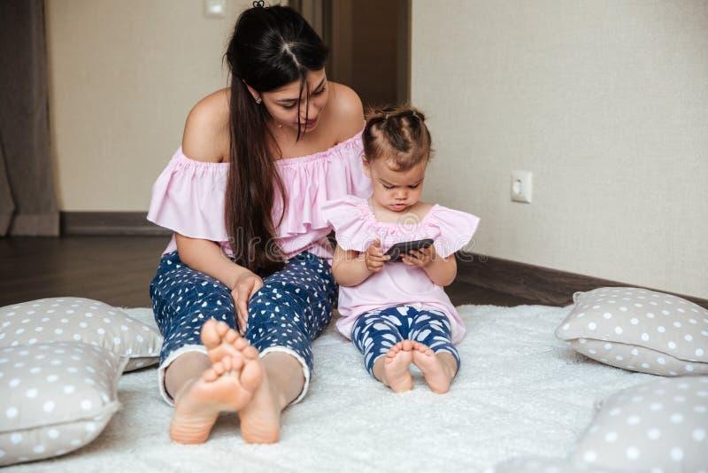 相当有她的使用手机的小女儿的年轻母亲 免版税库存照片