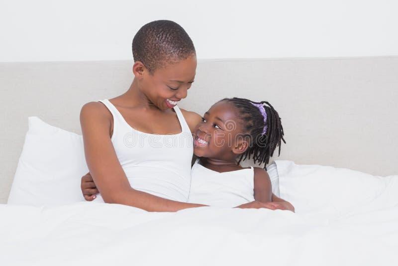相当有她的女儿的美丽的母亲在她的床上 免版税库存图片