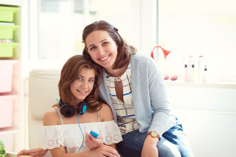 相当有她的tennager女儿的年轻母亲画象  免版税库存照片